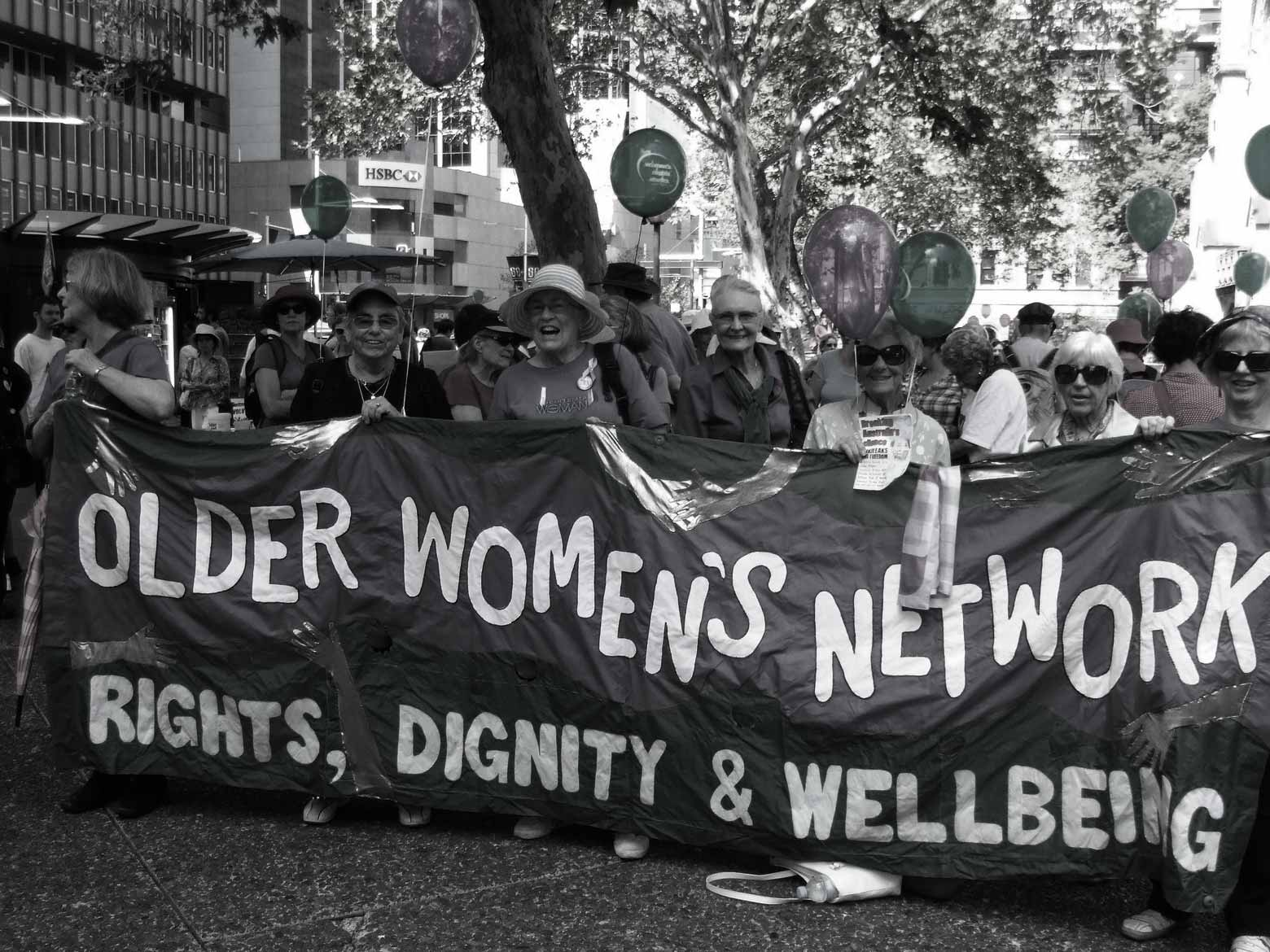 "Women marching, holding a banner with ""Older Women's Network"" written on it."
