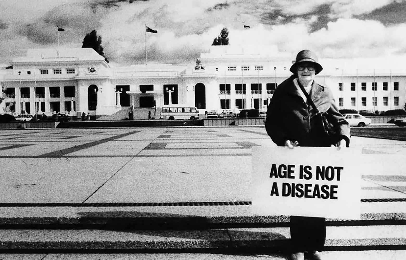 "1988 - A woman holding a placard in front of Parliament house, ""Age is not a disease""."
