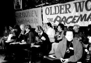 "1989 Woen sitting in front of a banner ""Older Women, the Pacemakers"""
