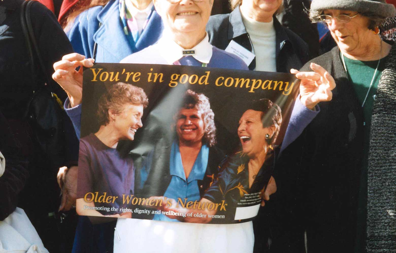 "1996 - an older woman holding poster of 3 women with the title ""You're in good company. Older Women's Network, Promoting the rights, dignity and wellbeing of older women"""