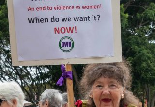"2002 - A woman holding a placard, ""What do we want? An end to violence vs women! When do we want it? NOW!"""