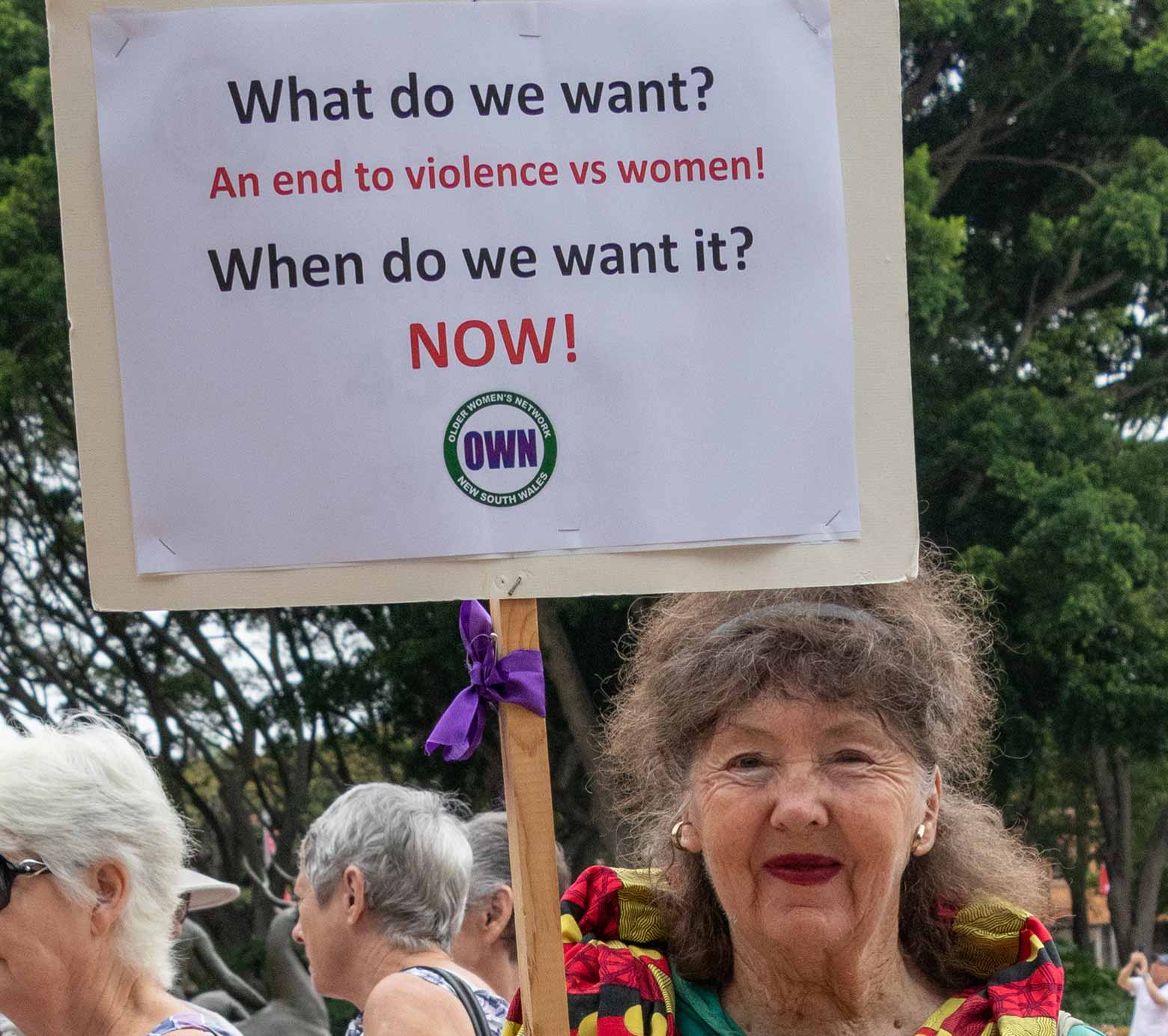 """2002 - A woman holding a placard, """"What do we want? An end to violence vs women! When do we want it? NOW!"""""""