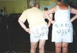 "2004 - Two theatre group performers (Peggy & Lucy), with ""Too Old? Never."" written on their shorts."