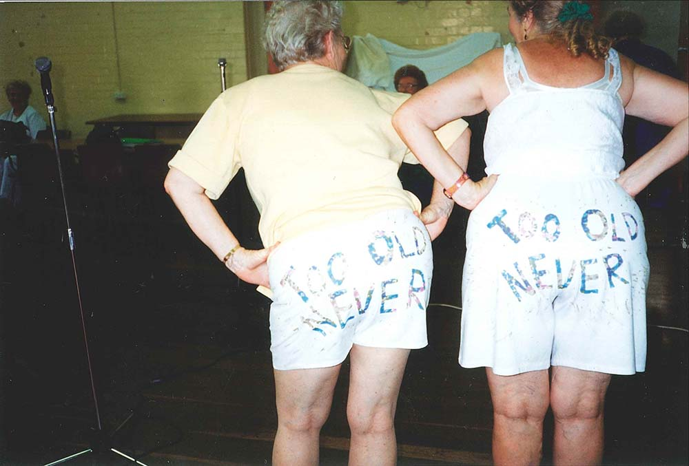 """2004 - Two theatre group performers (Peggy & Lucy), with """"Too Old? Never."""" written on their shorts."""