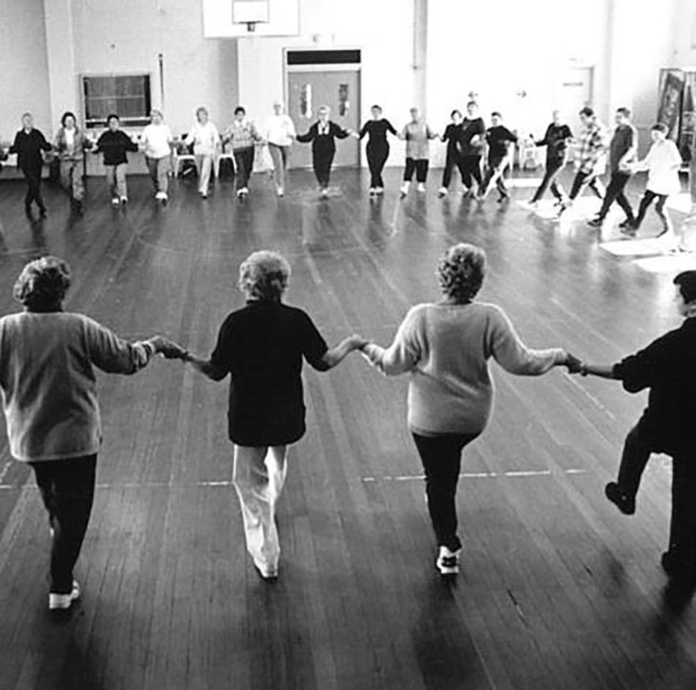 2005 - A large group of women holding hands in a large circle, line dancing