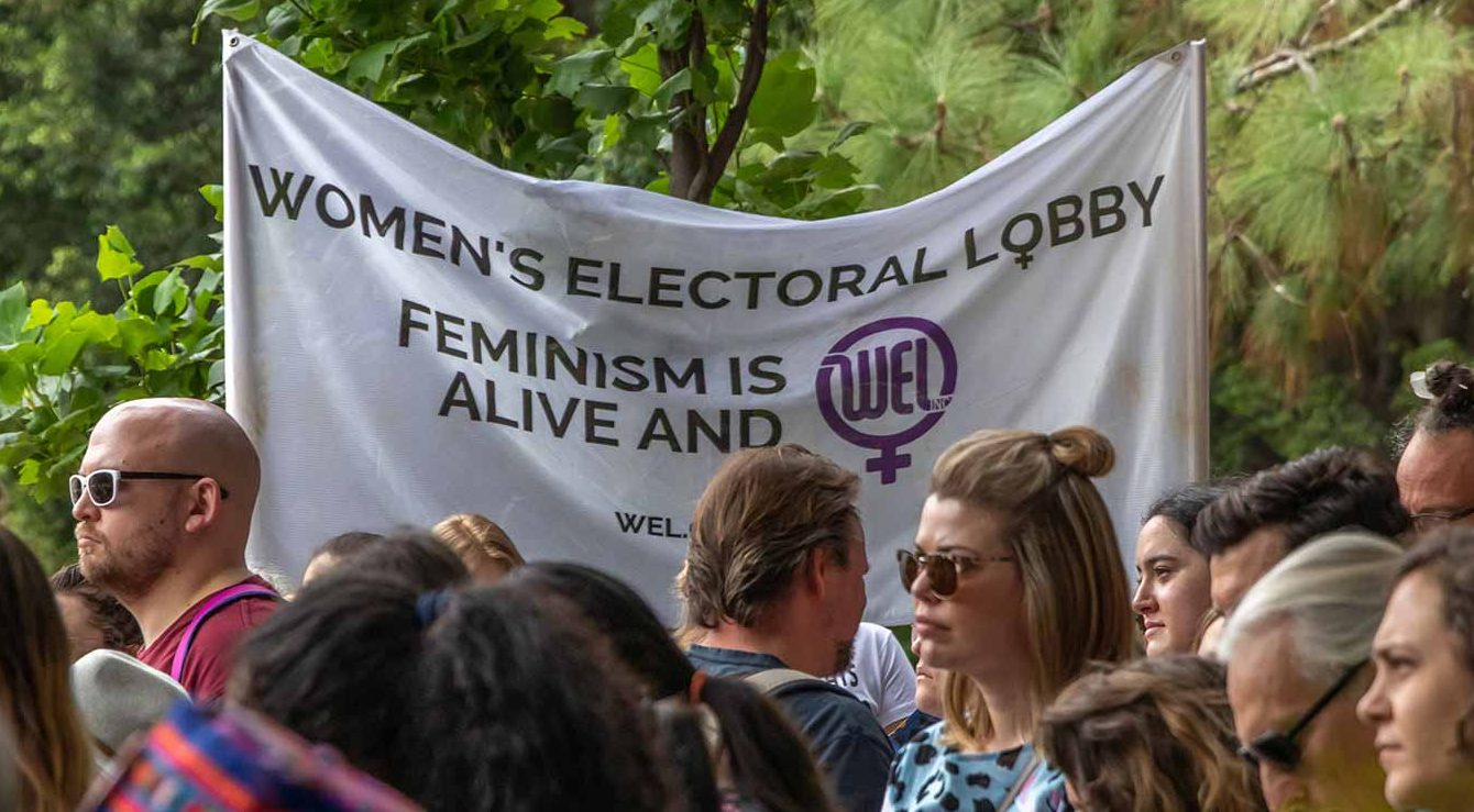 2016 - Women's Electoral Lobby banner being held up at a march, behind a group of people..