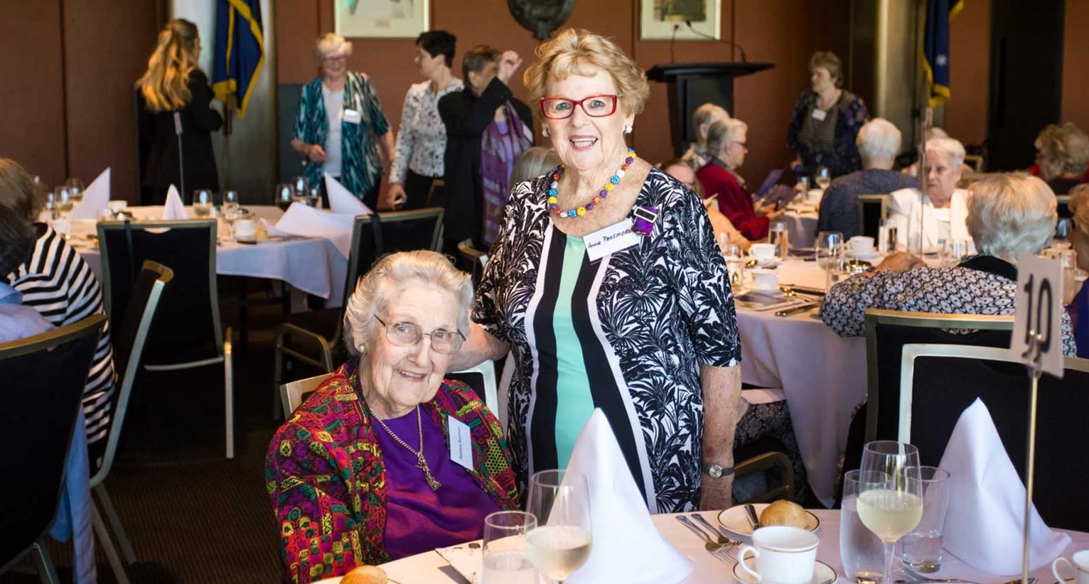 2017 - Two women (with others sitting at tables in the background) enjoying the OWN NSW 30th Birthday Luncheon