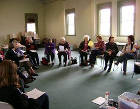 A large group of women in a room, sitting on chairs in a circle with paper in hand