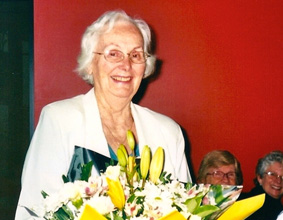 Margaret, holding a bouquet of yellow and white flowers