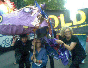 Three members from the NSW Theatre Group carrying a large purple paper dragon