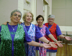 Four members of the NSW Theatre Group standing in a row with one arm outstretched