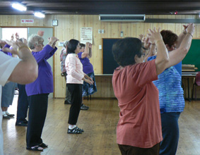 A group of women participating in a thai-chi class