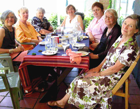 A group of older women sitting at a table eating lunch