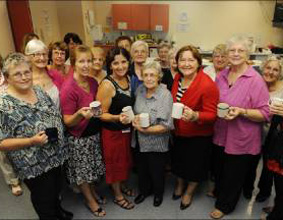 A large group of older women holding cups, posing for the camera