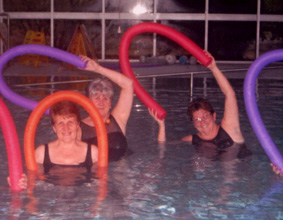 3 women in a pool holding pool noodles