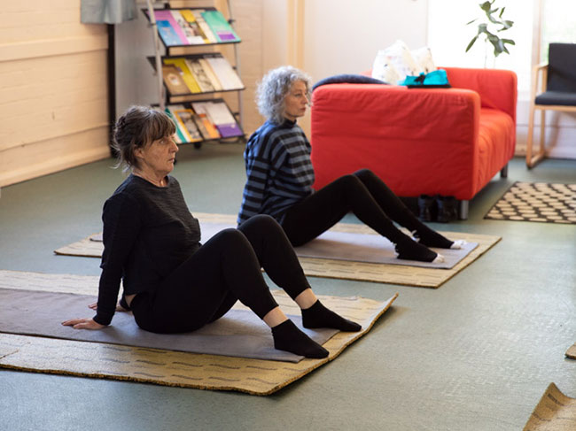 Mary doing a Yoga class, sitting on a mat