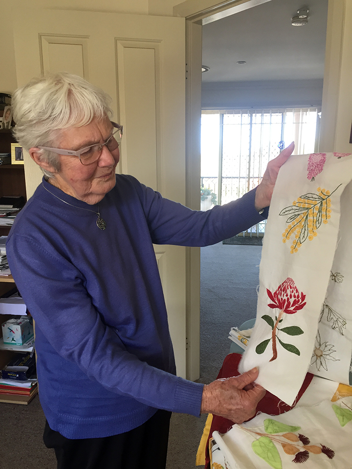 Barbara showing of her quilt embroidery of native flowers