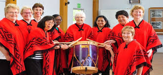 Barbara with a group of OWN women in red ponchos, drumming
