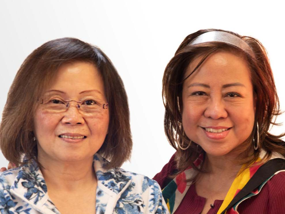 Two asian women facing the camera. The woman on the left is wearing glasses and a blue floral shirt. The woman on the right is wearing a pink headband and a red top with a scarf.