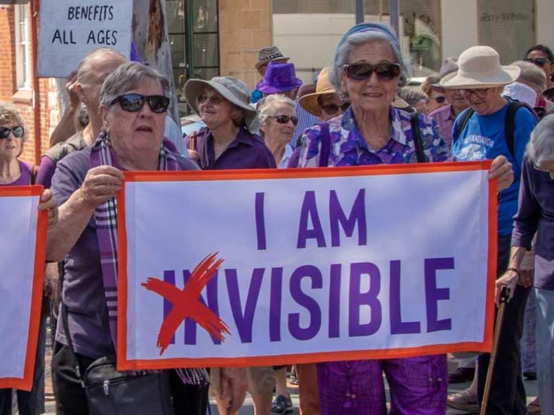 "Cate leading the International Day of the Older Person march, holding a banner, ""I am visible"""