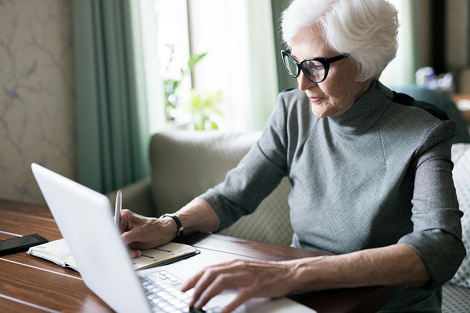 An older woman in eyeglasses planning her finances, she is making notes in notebook and typing on laptop