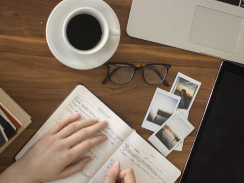 An overhead shot of a desk with a cup of coffee, reading glasses, photos and someone writing in a notebook