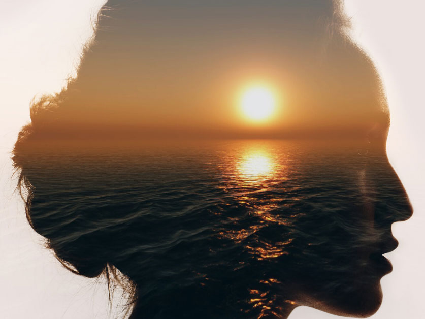 A silhouette of a woman's head with a sunset overlaid