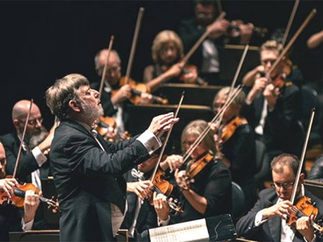 A conductor standing in front of an orchestra