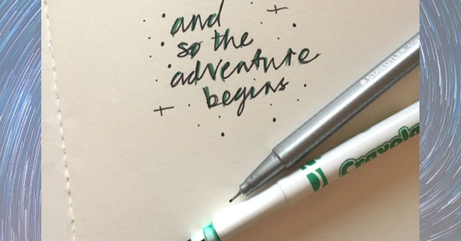 "2 pens resting on paper with the words ""and so the adventure begins"" written on it"